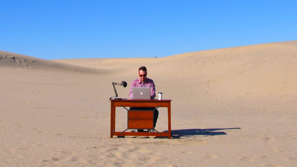 Location Rebel founder Sean Ogle working at his desk in the desert.